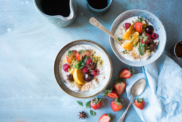 Two bowls filled with porridge and fruits on a blue background.
