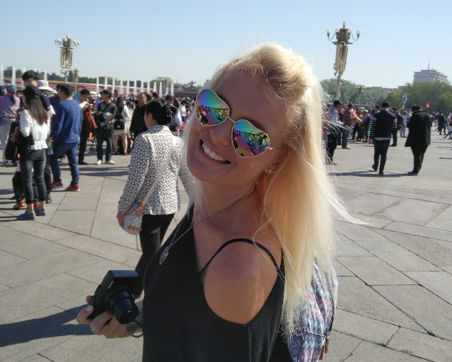 A blonde woman wearing sunglasses in a busy square.