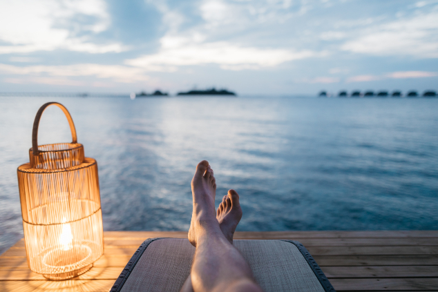Legs of a man relaxing next to the sea with a lamp.